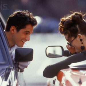 Young man in a car and young woman in a convertible